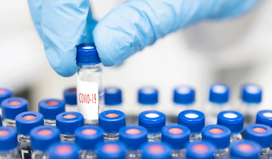 An image depicting vials with a hand pulling one from the group that is labeled Covid-19